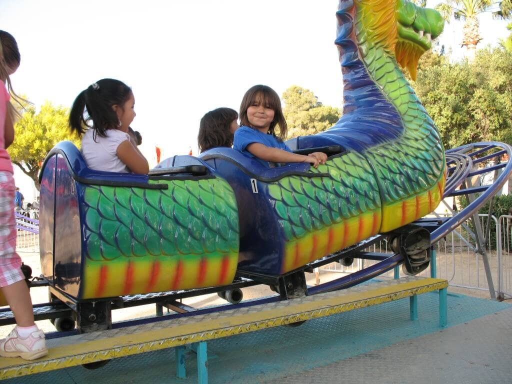 Young children on a dragon themed kiddie rollercoaster