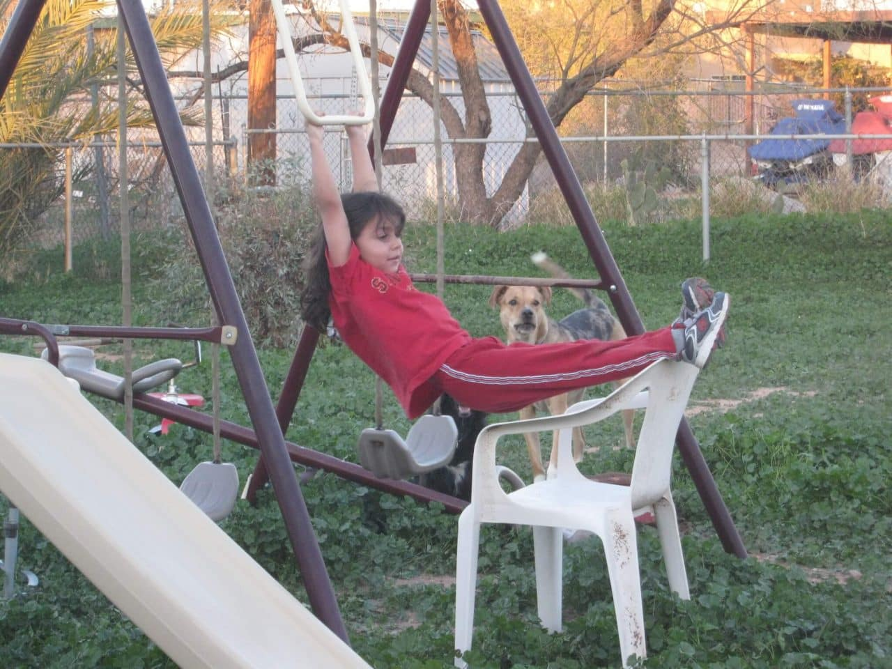 Young child swinging on the trapeze bar of a swing set