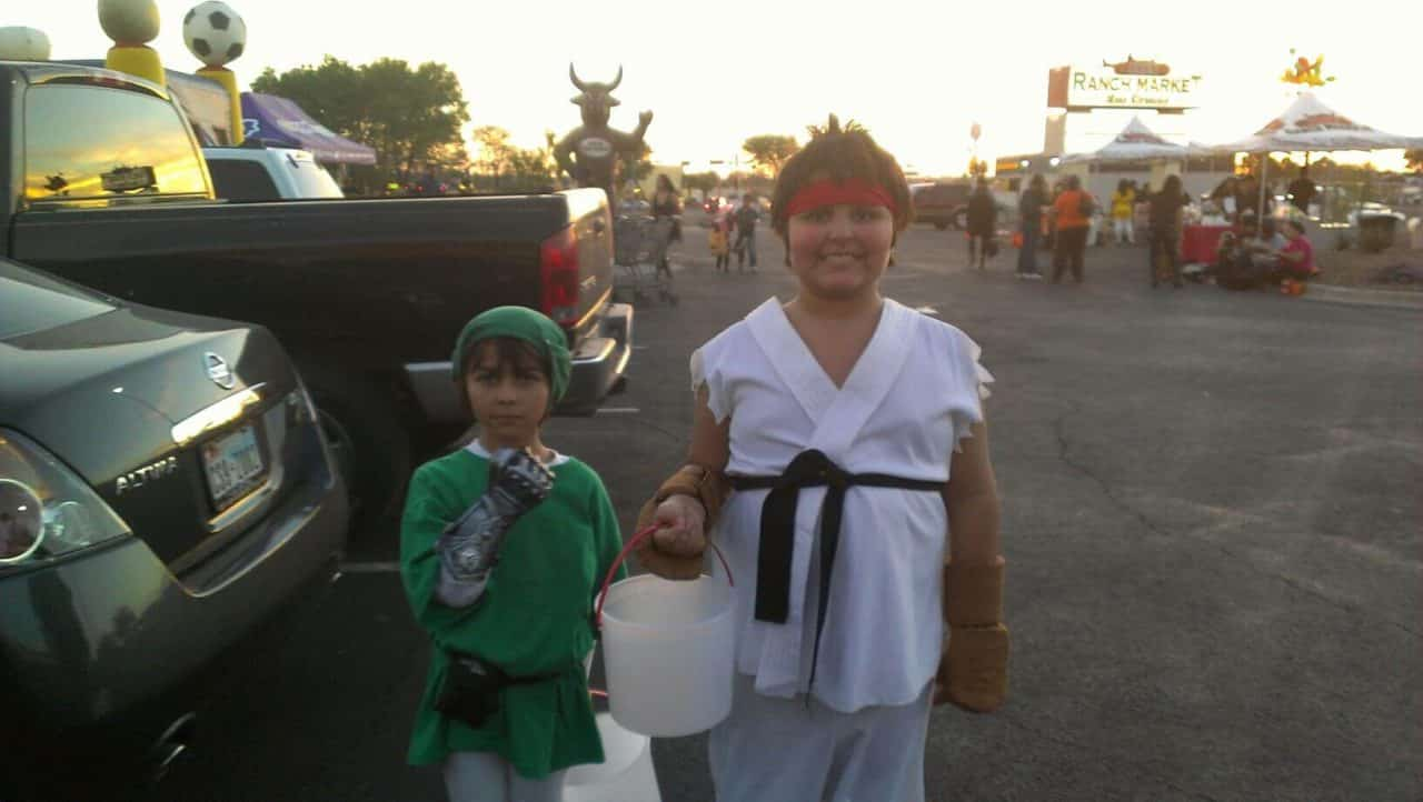 Two young children in Halloween costumes. One as Link from the Zelda game franchise while the other is Ryu from the Street Fighter game franchise