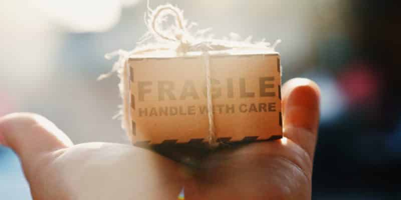 person holding box marked fragile