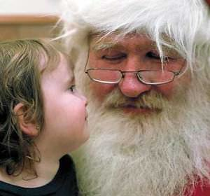 Riley Whelan, 2, and Larry Geiger as Santa contemplate each other last week at the United Way office.