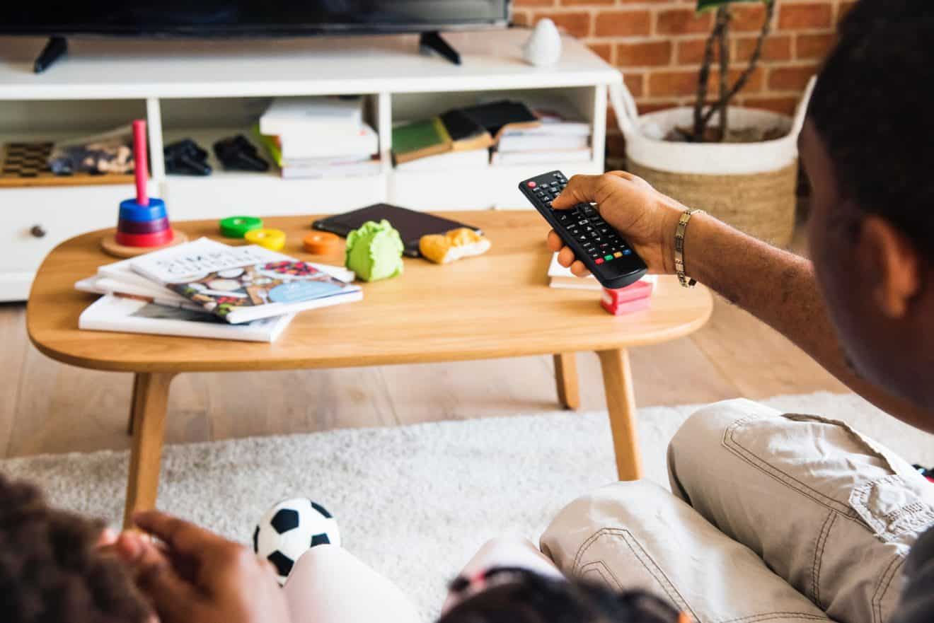 person pointing remote control towards flat screen television