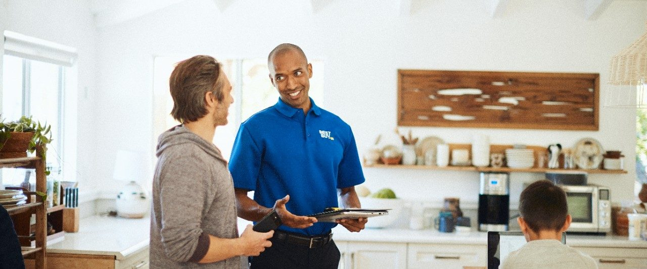 A Best buy employee providing an in-home consultation in a homeowner's living room