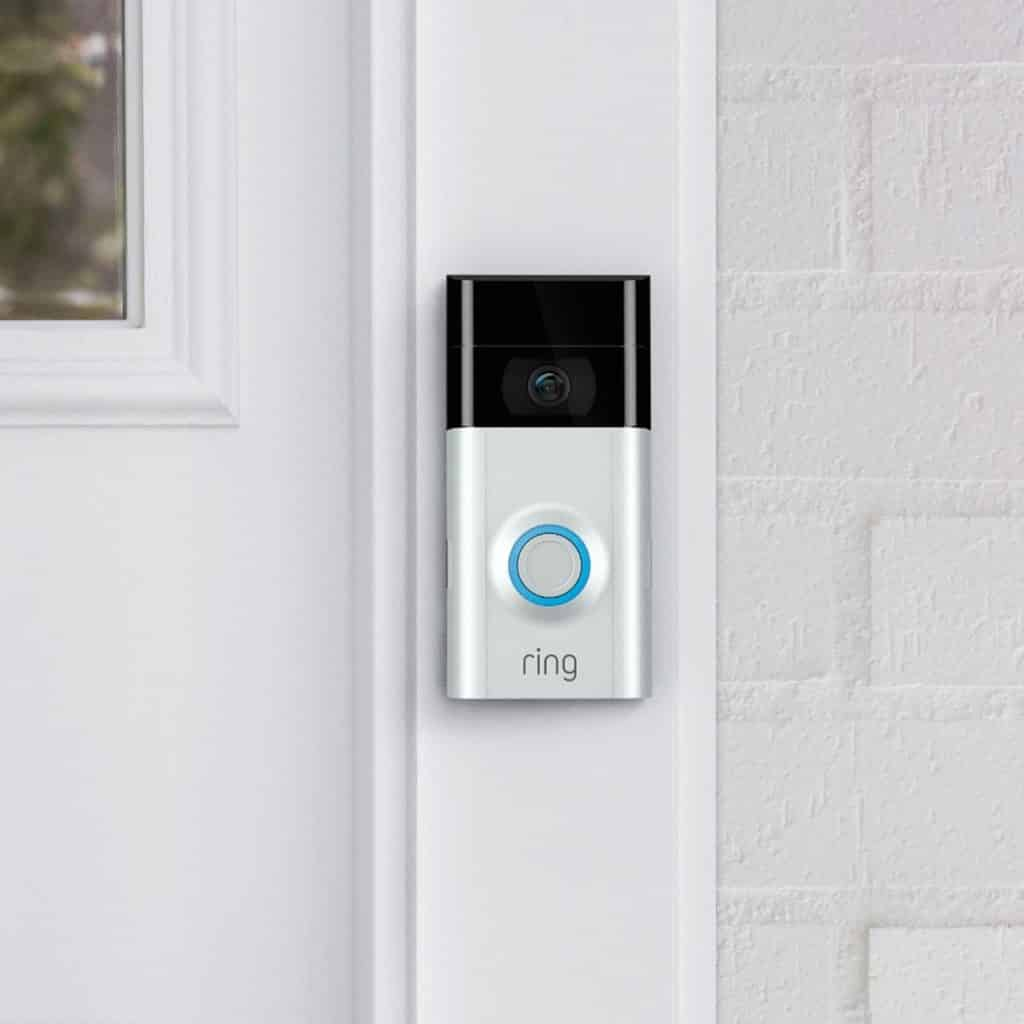 Ring doorbell installed on the white frame of a front door entrance