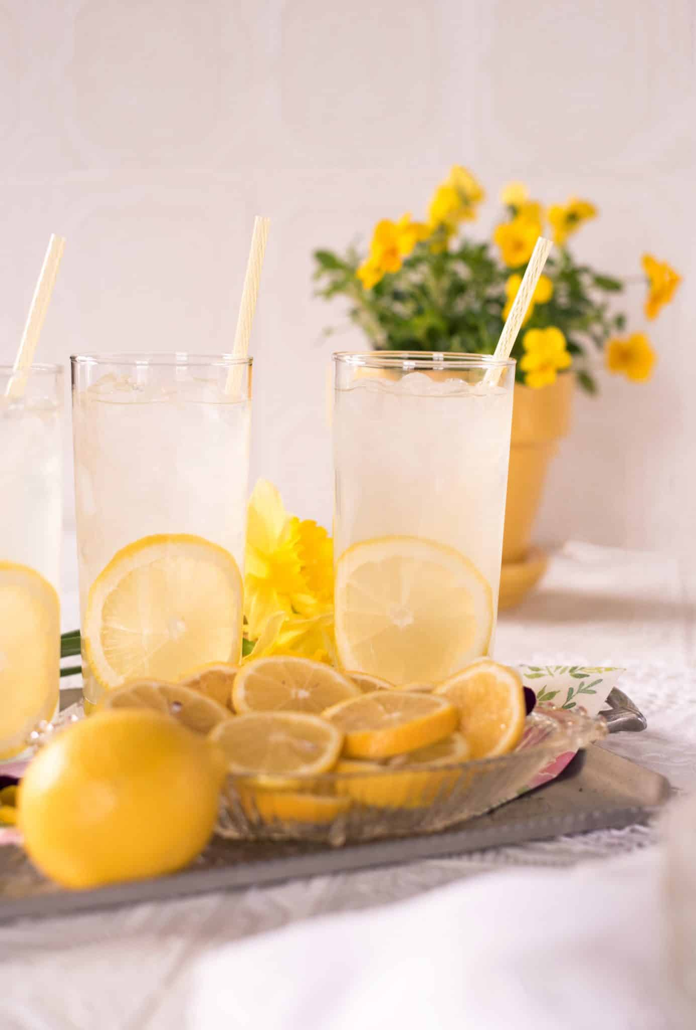 Serving tray with three glasses of lemonade with a slice of lemon inside each glass